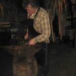 Le forgeron fait des outils: il met le fer dans le feu puis il tape avec le marteau